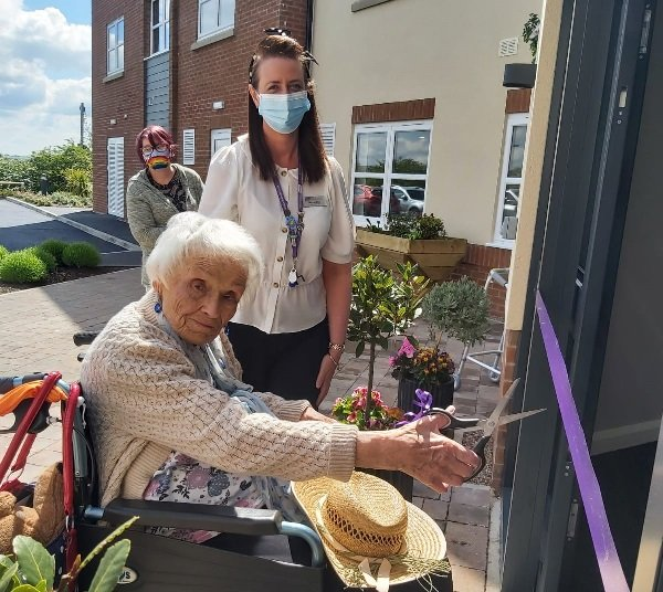 Marjorie Fern cut a ceremonial ribbon to mark being the first resident to move into Littleton Lodge care home on  Bishop Street in Hednesford.